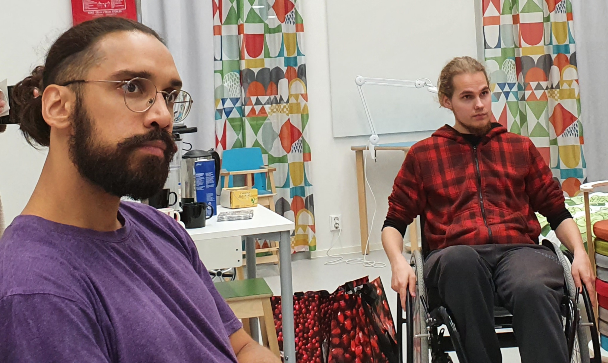 Mies istuu tuolilla, toinen mies istuu pyörätuolissa