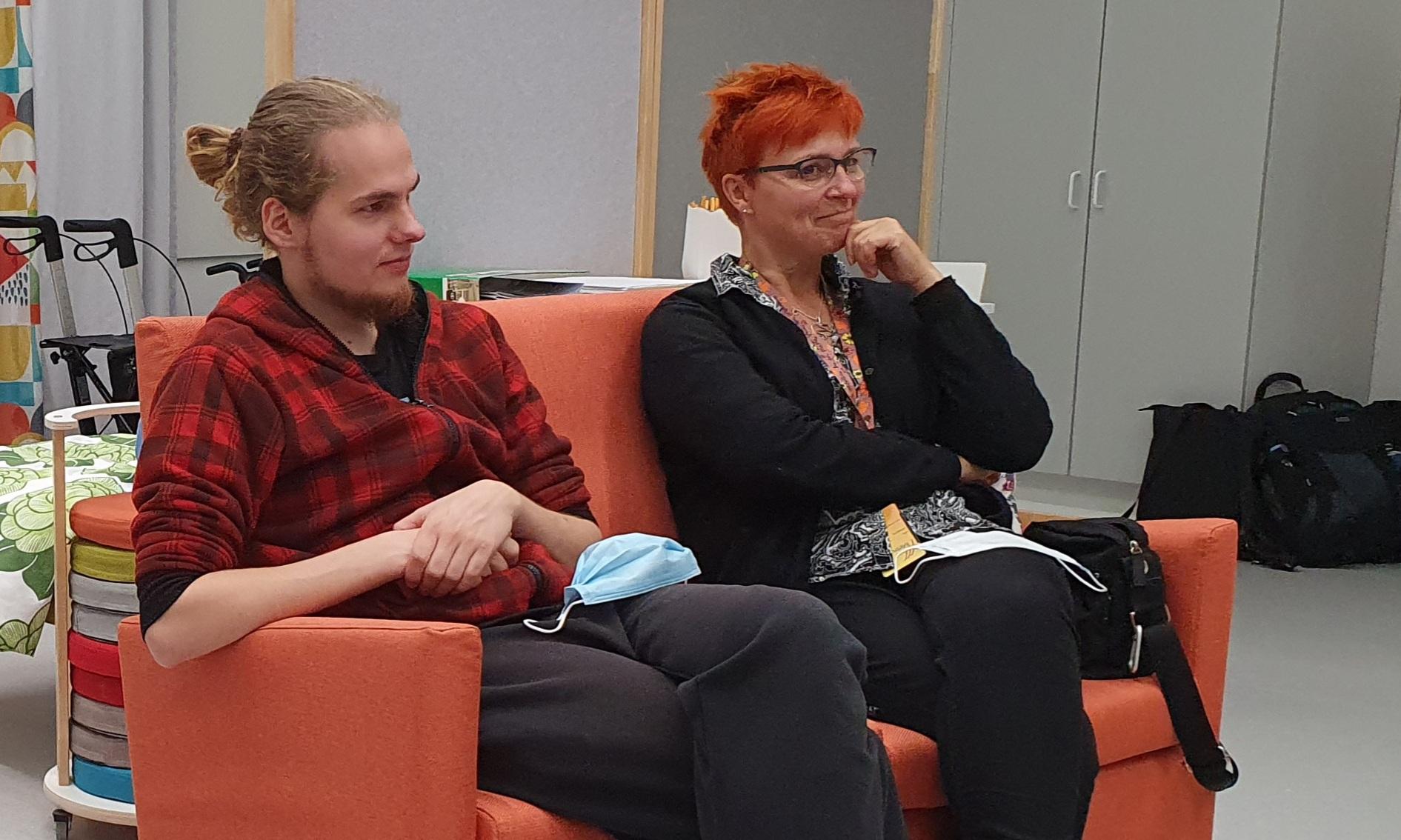 Nuori mies ja nainen istuvat sohvalla