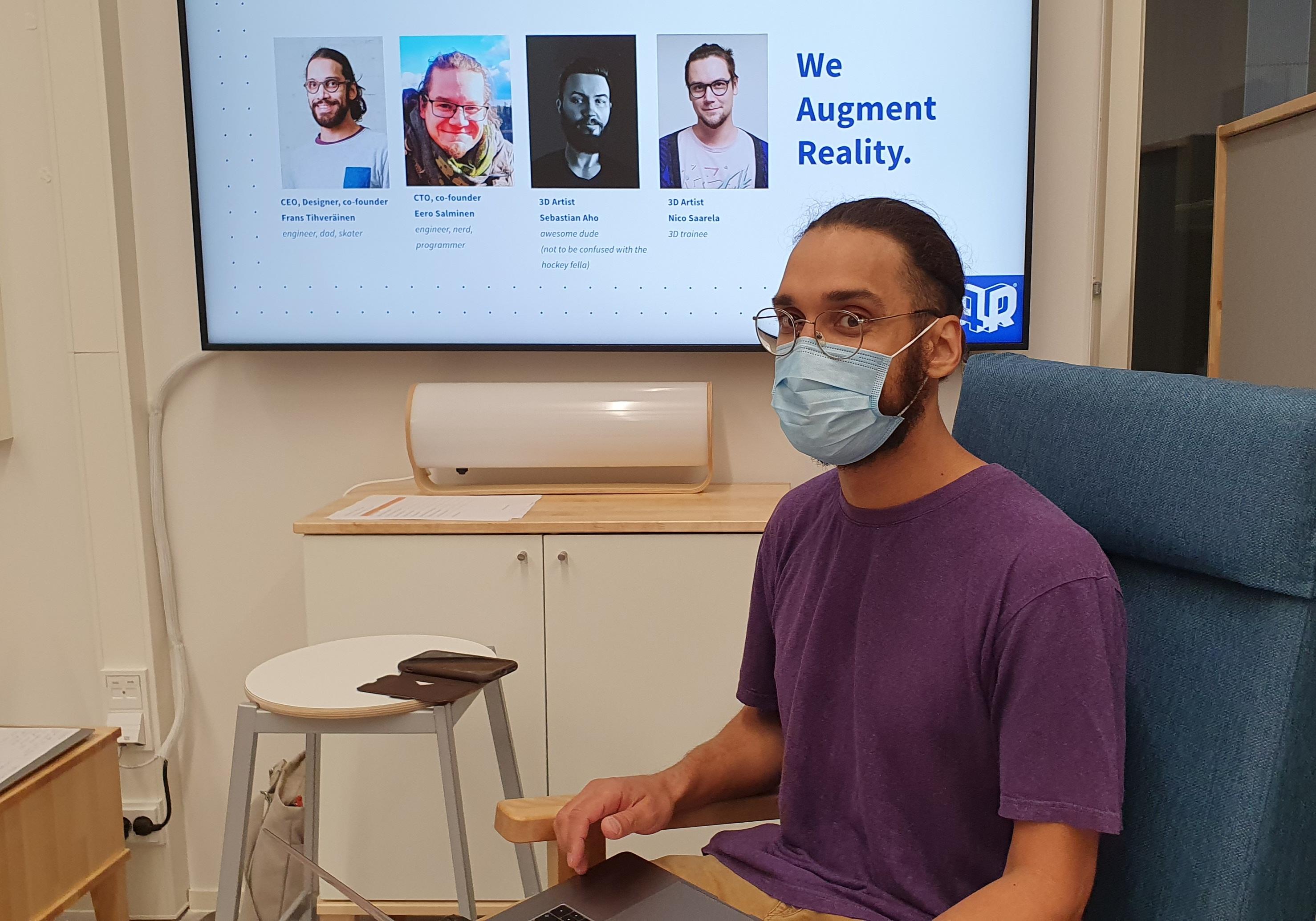 Mies maski päällä, taustalla screen.