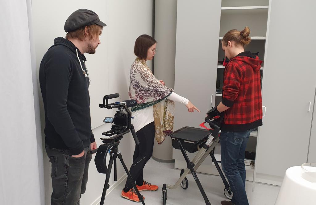 Videokuvaaja seisoo, nainen osoittaa sormella, mies rollaattorin kanssa