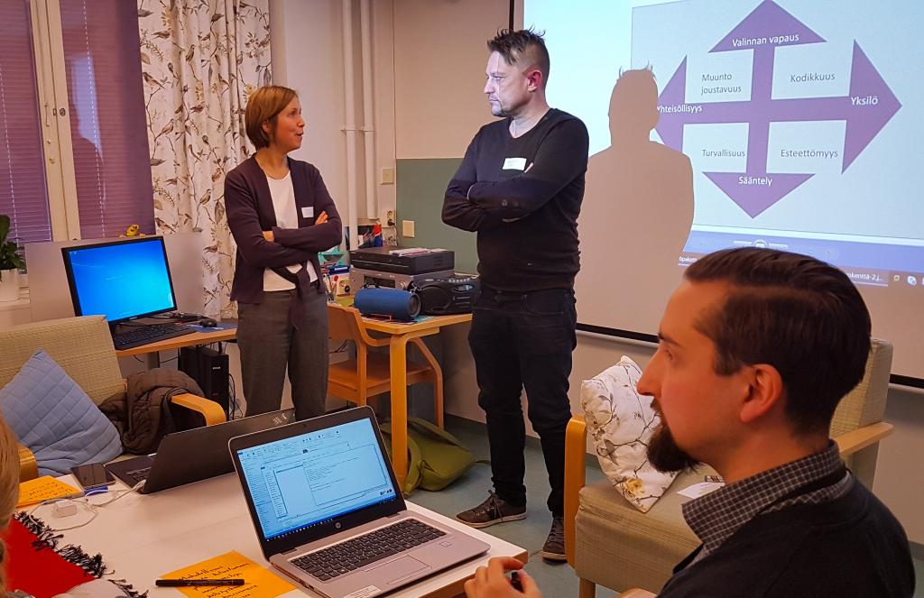 Nainen ja mies seisovat ja keskustelevat, Mies istuu pöydän ääressä tietokone edessään.