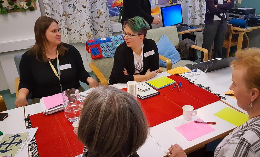 Kaksi naista keskustelee pöydän ääressä. Kaksi naista kuuntelee heitä.
