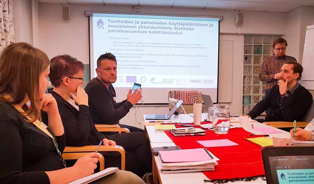 Mies esittelee kännykkää, neljä ihmistä kuuntelee pöydän ääressä.