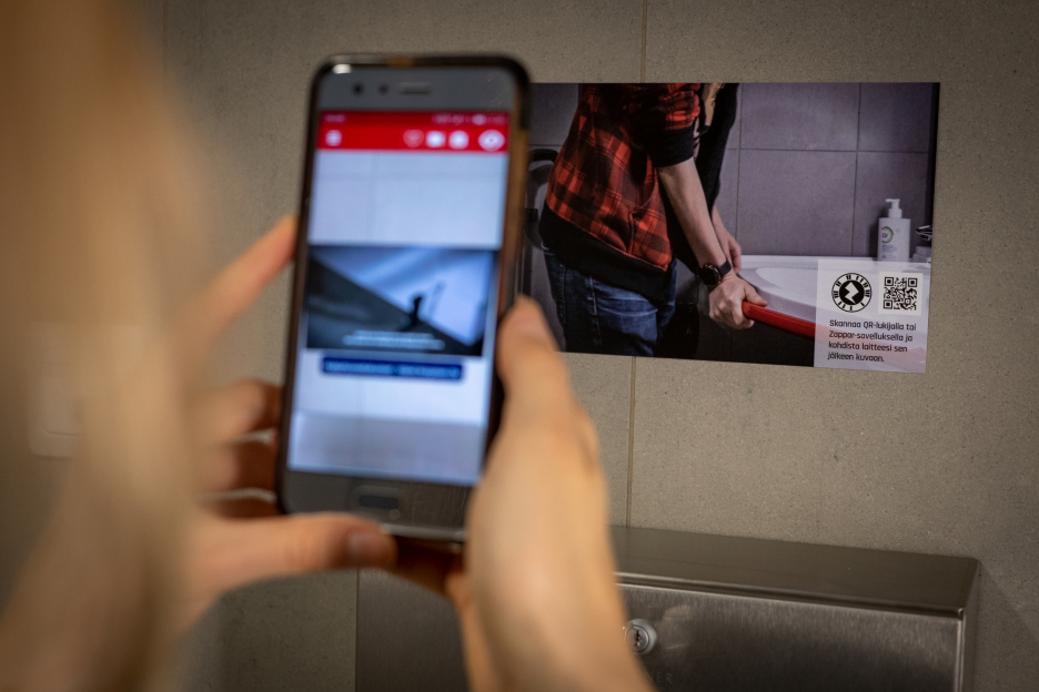 Woman points at a picture on the wall with a mobile phone