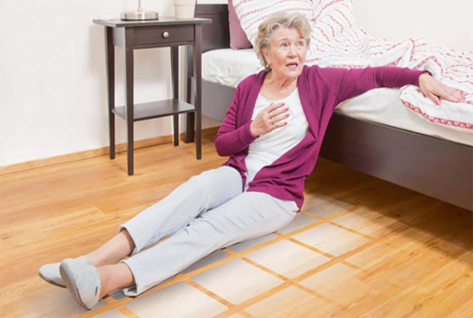 Woman sitting on a floor next to bed