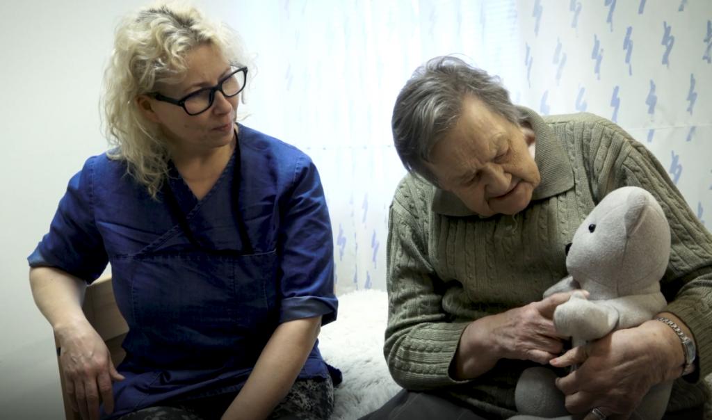 Hoitaja ja iäkäs nainen istuvat sängyllä, iäkäs nainen pitelee nallea.