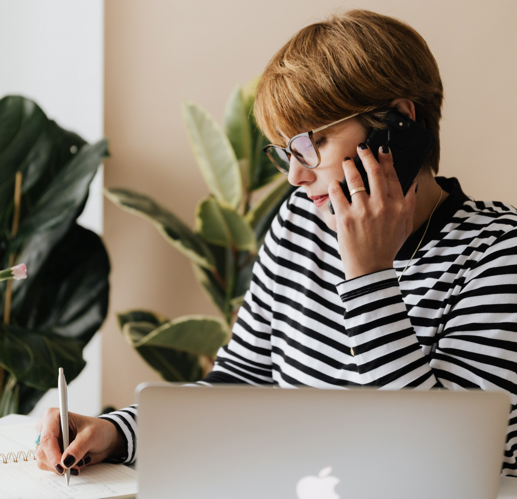 Nainen puhuu puhelimessa pöydän ääressä ja kirjoittaa kynällä, edessään tietokone.