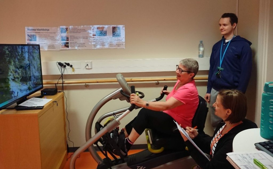 A woman using the exercise software and two students watching her.