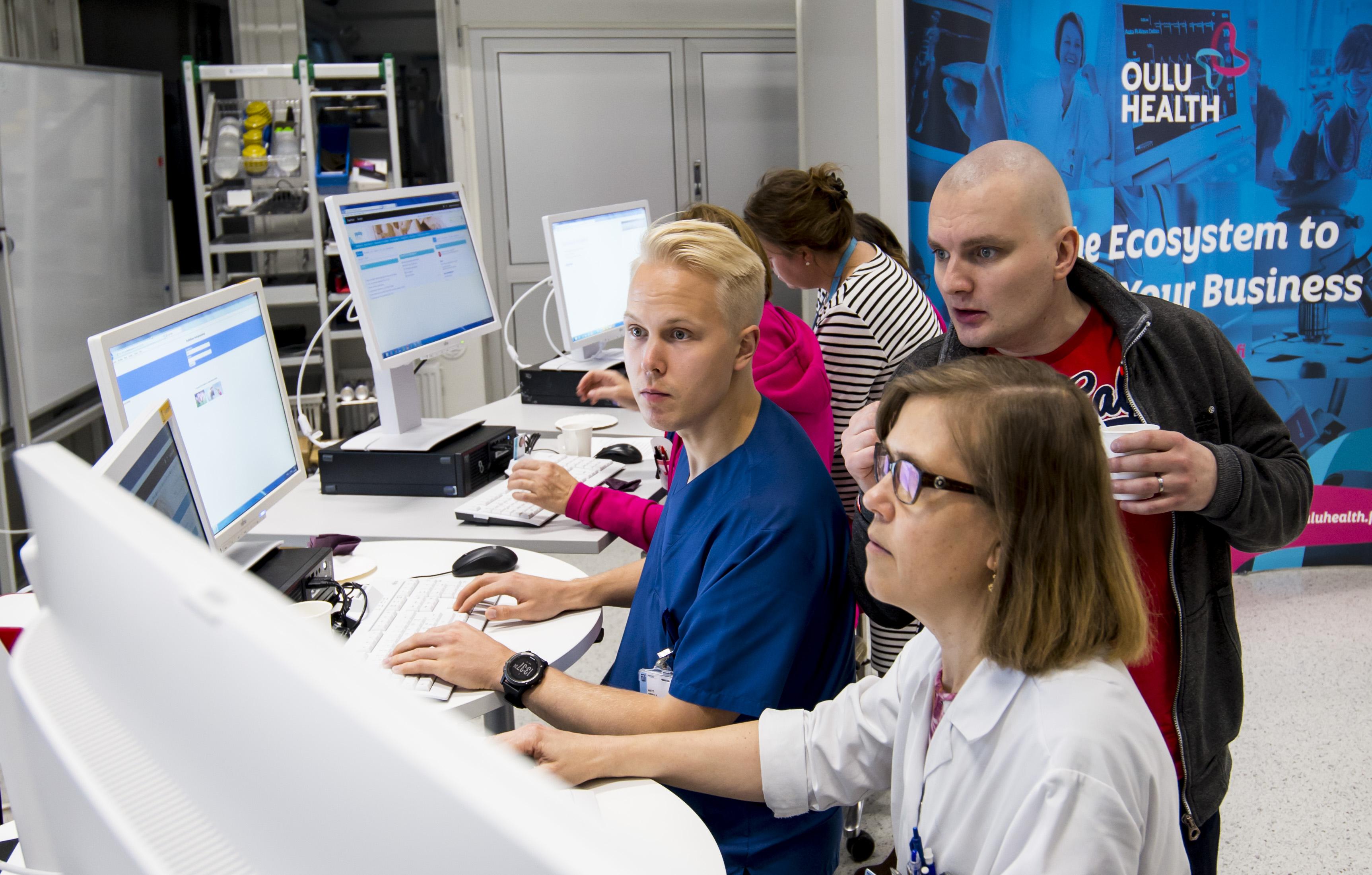 Ryhmä ihmisiä katsoo tietokonetta laboratoriossa.