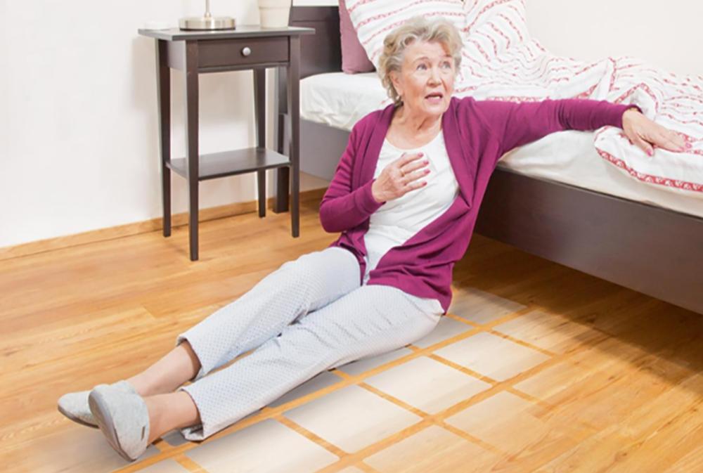 Nainen istuu lattialla sängyn vieressä