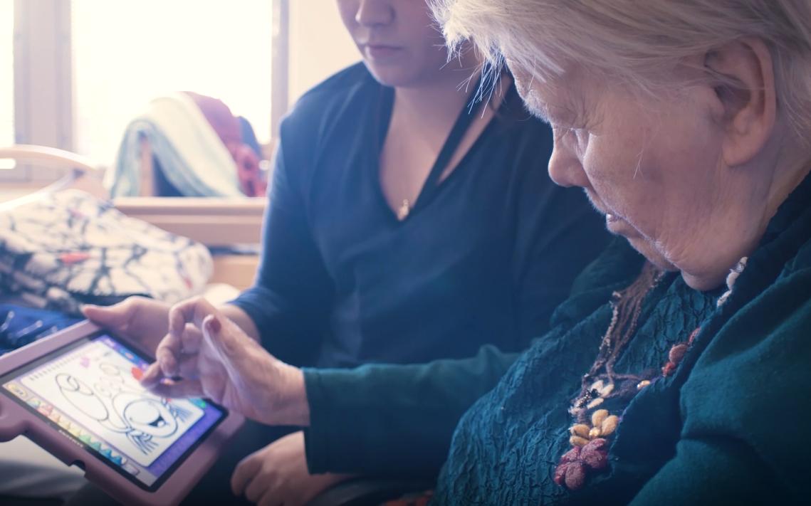 Vanha ja nuori nainen käyttävät tablettia.