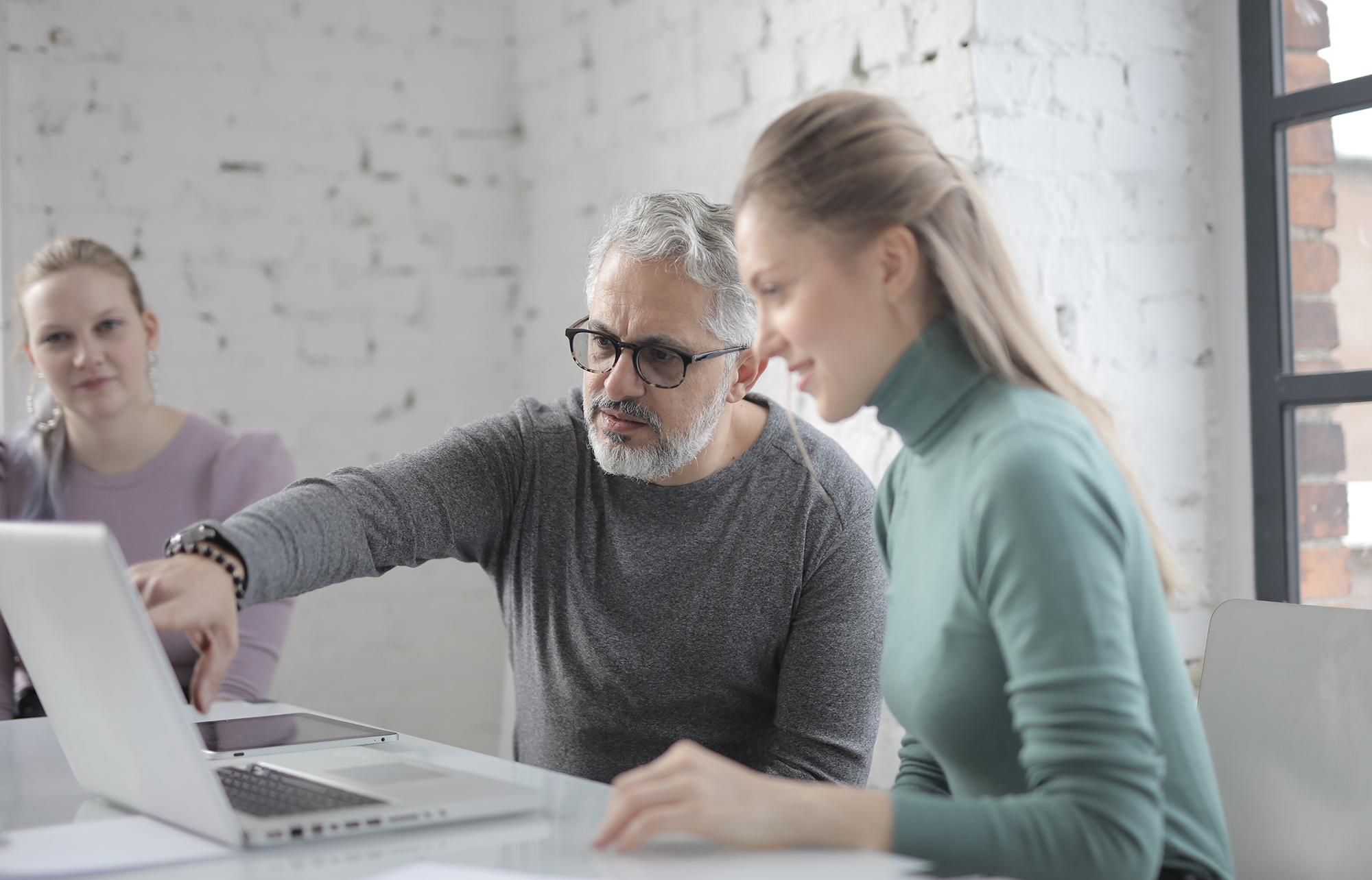 Iäkäs mies ja nuori nainen katsovat tietokonetta.