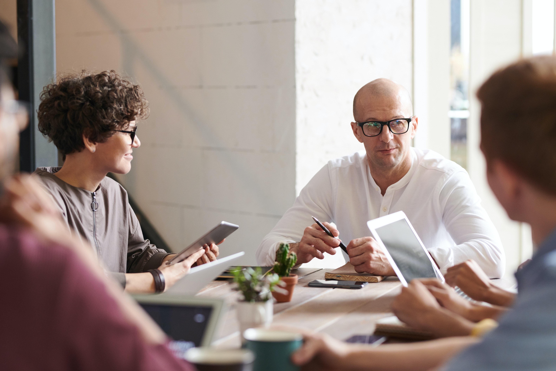 Ryhmä ihmisiä keskustelee pöydän ääressä.