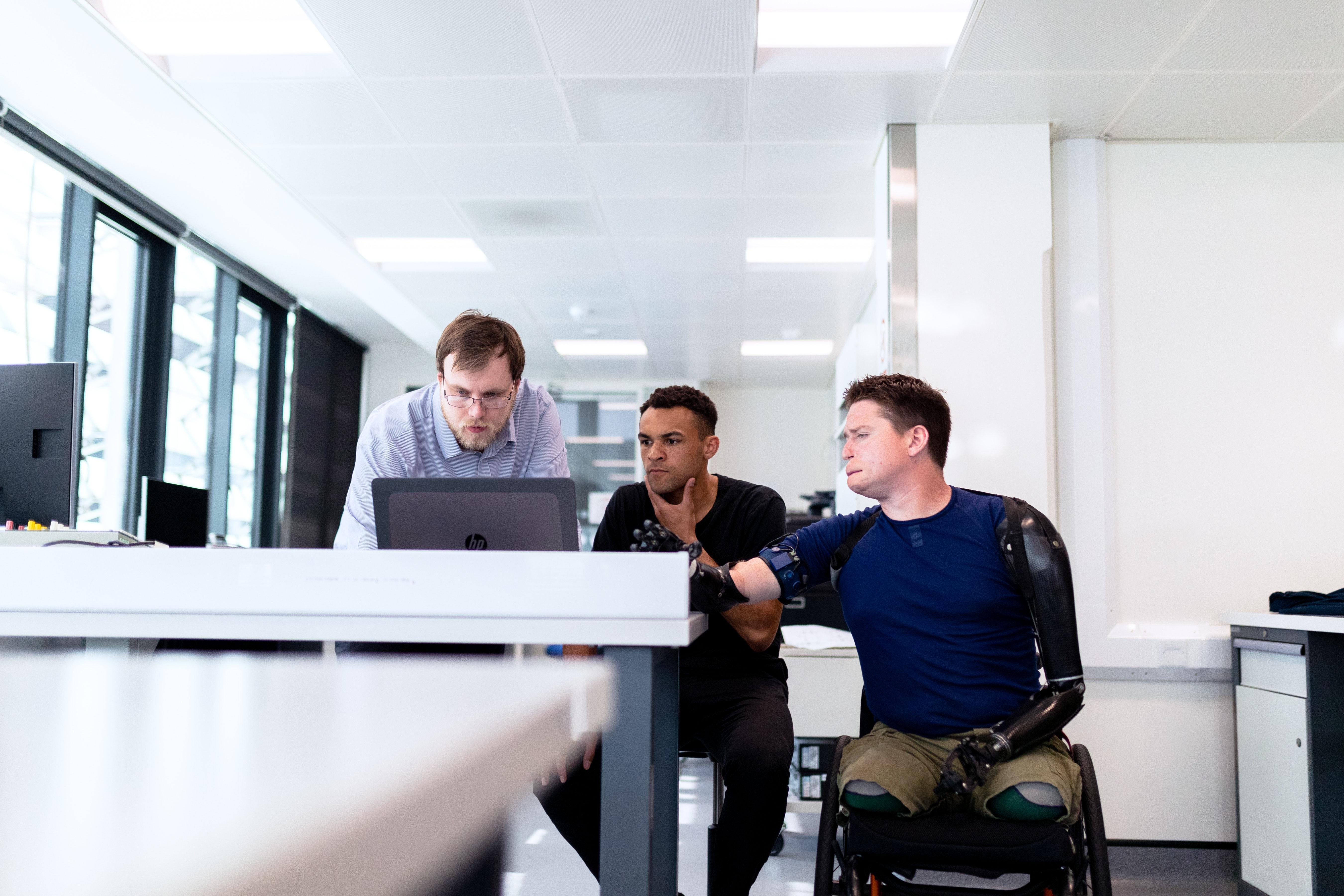 Pyörätuolissa istuva mies ja kaksi muuta miestä tietokoneen äärellä.
