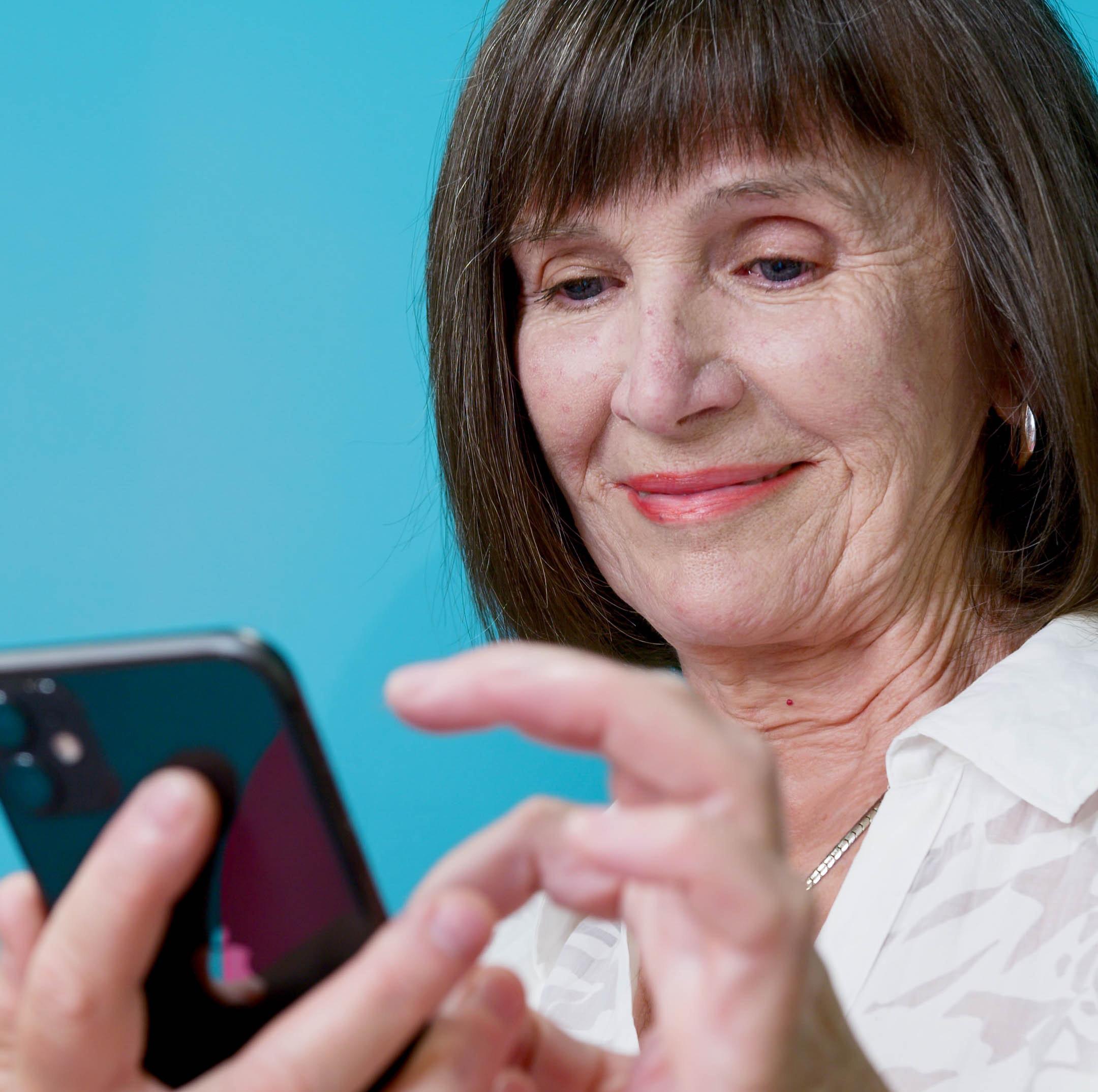 iäkäs nainen näpyttelee kännykkää