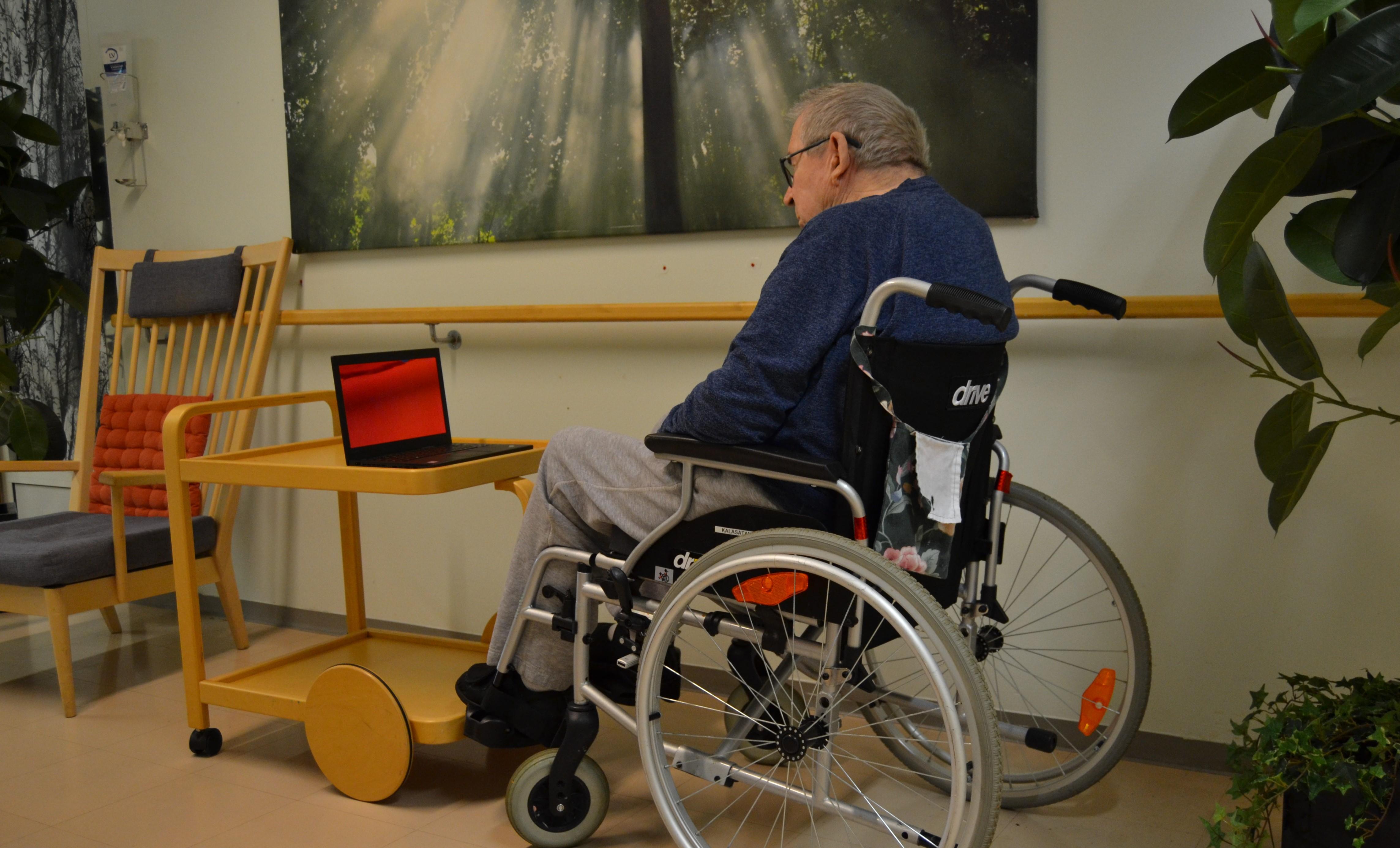 Vanhus istuu pyörätuolissa ja katsoo videopuhelua.